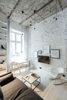 Beautiful living room idea with white brick wall, pendant light bulbs, light floor and wishbone chairs