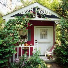 Detailed scrollwork on the porch of this playhouse potting shed brings a playful touch to the structure. Heart-shape cutouts in the shutters, a Dutch door with lace curtains, and a white wicker chair complement the casual country look.