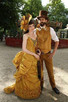 Gorgeous Golden Couple (woman wearing yellow/gold victorian bustle dress and hat, man wearing gold/yellow waistcoat, ascot, top hat, trousers, shirt) - For costume tutorials, clothing guide, fashion inspiration photo gallery, calendar of Steampunk events, & more, visit SteampunkFashionGuide.com