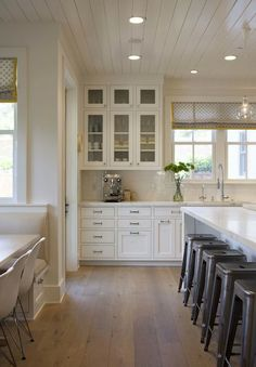 .all white kitchen with mid-tone wide plank hardwood floors, glass front inset cabinets, marble counters, subway tile back splash, industrial style faucet & appliances, & window with roman shade over wide sink