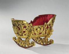 Carved gilt wood rocking cradle lined with buttoned red silk edged with fringing; carved with scrolling strapwork, putto masks, coats of arms at the ends and foliage, with a background of ochre paint; caryatid-type figures above the scrolling rockers.