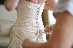 3078954-914470-helping-the-bride-to-put-her-wedding-dress-on.jpg 480×319 pixels