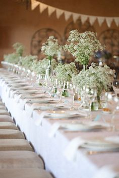 Cost effective and stunning wedding flower arrangements - by varying the alfabridal.com  height of the arrangements the gypsophila or baby's breath is used to great effect on this long table