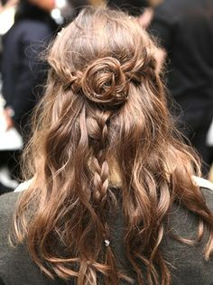 Wrap small sections of hair around a two-inch curling iron for sexy, unfussy bends. Then, brush them out, for a more natural appearance, and then braid a three-inch section of hair from above each ear to the back of the head. Once they meet in the centre, pin them into a messy little 'rosette' bun, and spray a layer of hairspray over the top.