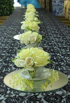 avalant flower arrangement in a cup with saucer mirror and a sprinkling of yellow diamond