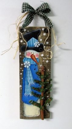 Reclaimed Barn Wood with Painted Snowman, Snowman with Gingerbread and Cookie Cutter Christmas Tree, Hand or Tole Painted, Green Tree This whimsical Snowman with his Evergreen Tree all decorated with Gingerbread cookies and Cookie cutters will welcome any winter time guests! This design is based on a Monika Brint tole painting pattern. It has been adjusted and adapted to fit on to a piece of old reclaimed barn wood. The barn wood measures 16 inches tall x 5 1/2 inches wide and is 19 inc...