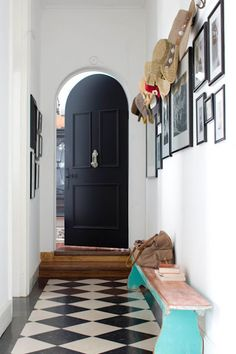A narrow entry with style,black front door & checkered floor