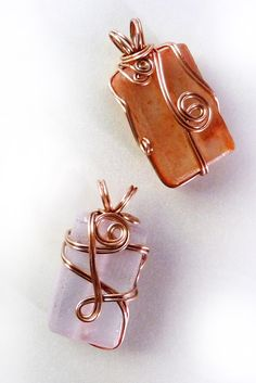 So pretty! Translucent orange recycled bottle glass beautifully wire wrapped in copper swirls. The colored glass has an almost frosty matte finish and the copper wrap is brightly polished to a rose gold finish.