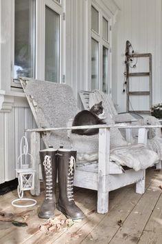 Katt på veranda i stol med lammskinn.