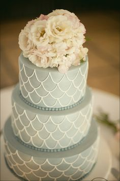 A simple wedding cake in pale blue with a white scale-like icing and fresh flowers. Photo by Toole Art.