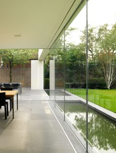 Lovely sheer glass extension in Wimbledon with doors only in each end which makes sense in the British weather_And means a water feature can be the focus of the room rather than looking into garden furniture on a terrace all year long. Love it!