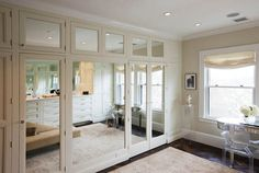 Luxurious walk-in closet with mirrored closet doors accented with nickel pulls alongside a kidney shaped mirrored vanity lined with a Starck Ghost Chair atop parquet floors layered with a faded neutral rug.