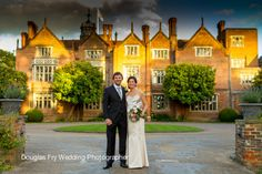 Couple infront of Great Fosters - wedding photograph