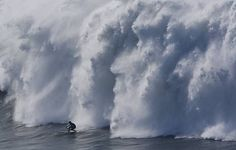 A surfer coasts in front of crashing waves during the seminfinals of the Mavericks Surf Contest in Half Moon Bay on Saturday. Photo: Adam La...