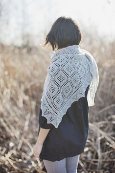 "This triangular shawl is constructed using a combination of traditional and modern Estonian construction methods and is adorned with an Estonian ""Cube & Spruce"" allover motif. Worked in a pale shade of grey, it reminds us of snowy woods during Winter. Nupp clusters add subtle texture to the central triangle and a lacy border makes …"