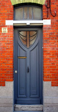 Slate-lavender-grey-blue door with lime brick above, red brick surround, leaded frosted pane, hint of Rennie MacIntosh