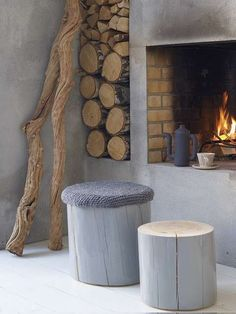 Open haard beton look - Woontrendz I love the icy gray, the raw wood, and the warmth of the fire.