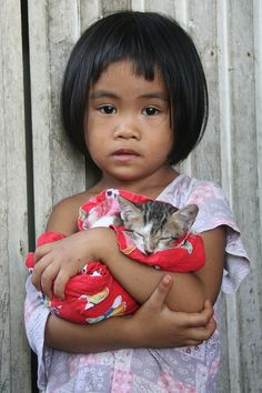 A young girl cradling her kitty, she is so beautiful, I would love to hold her along with her kitten.