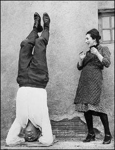 December 1963: Italian actress Valentina Cortese smiles at actor Anthony Quinn relaxing in a yoga position in Rome.