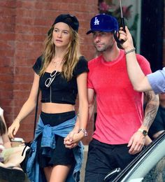 Adam Levine and Behati Prinsloo Adam Levine and Behati Prinsloo New York City, New York - September 2, 2013. The rain must have made her clothes shrink.
