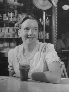 A girl having a soda at a drug store, US, 1945. Source