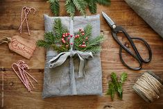 Still life of homemade wrapped christmas present wrapped in linen with pine and berries