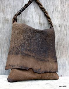Made from a heavy cowhide with a matte finish and lots of rustic character. Bag is 13 tall and 10 across. Unlined, sued side of the leather inside. One drop in leather pocket. 34 rugged and twisted strap has a sixteen inch drop. One of a kind.