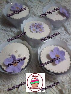 Cupcakes de vainilla, decorados con flores lila.