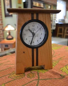 """This Craftsman Desk clock is one of our best sellers.  Made with Cherry wood with walnut inlays by Desmond Suarez of Asheville, NC.    SIZE: 7.5""""H x 5.5""""W x 2.5""""D  $55."""