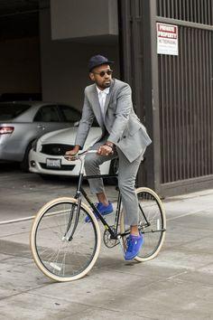 Black Baseball Cap  — Dark Brown Sunglasses  — White Dress Shirt  — Grey Double Breasted Blazer  — Grey Dress Pants  — Blue Suede Low Top Sneakers