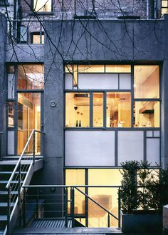 Greenwich Village Townhouse by SPG Architects  The rear façade was built anew of glass and steel with cement board infill panels, which hide the kitchen cabinets.
