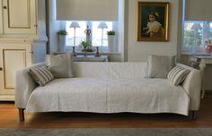 Sofa mit weißen Armlehnhussen und weißem Plaid, dazu grau-weiße Kissen