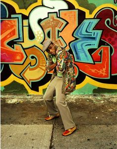 Mos Def posing in front of graffiti. His shirt is as colorful as the wall.
