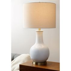 Add a touch of understated elegance to your living room with this white ceramic lamp from Abbyson Living. This table lamp features a simple curved gourd design that melds with both modern and traditio