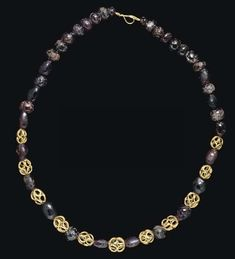 A ROMAN GOLD AND GARNET BEAD NECKLACE   CIRCA 3RD-4TH CENTURY A.D.   Composed of eleven openwork gold beads formed from loops of plain wire, interspersed with thirty-six globular garnet beads; strung on a modern wire with looped ends