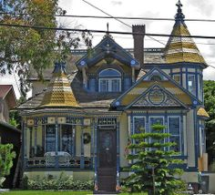 This playful little house looks like a Queen Anne Victorian, but if you examine the roof you can see the outlines of its true nature.