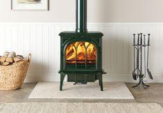 Le poêle à bois Huntingdon 35 de Stovax en vert laurier avec porte gothique et brûlant des bûches.