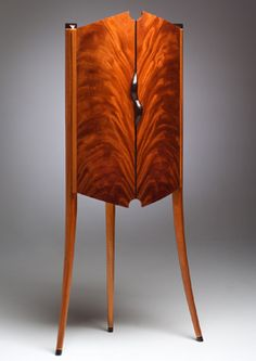 Mahogany solids and veneer, figured maple, cocobolo, macassar ebony.    This curved-front corner cabinet provides an elegant storage solution that is visually bold but light, and minimal in footprint. By Michael Singer