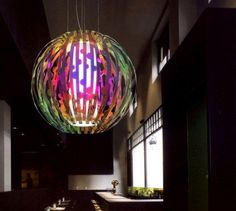 Popsy:    ::    The Ball light – but different. Strips of 'radiant' acrylic from Germany are cut and formed to create a cage around the central opal light tube. As you walk around this piece the 'radiant' material changes colour from pink to orange to green and so on. A beautiful piece. Dimensions shown 1000mm diameter; available in almost any size. Design: Conrad Johnsson