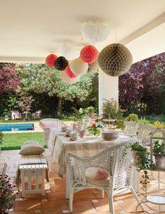 mesa comedor exterior y banco blanco y bolas guirnalda en el techo 00383976