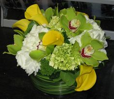 This is a floral arrangement that features yellow miniature calla lilies, green cymbidium orchid with green and white hydrangea.