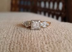 This Stunning Delicate Diamond Ring features an Antique Two Toned White and Yellow 14 K Gold Setting. Featuring a center .25 carat Diamond with