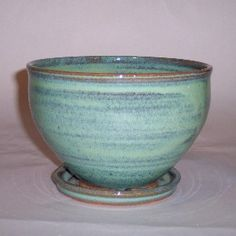 The hand thrown standing planters or cache pots have a hole in the bottom and come with a dish to catch extra liquid when watering.  They also hold about a quart and larger ones can be special ordered.     The planters come in attractive glazes which provide a beautiful compliment for your plants.     These pottery planters are handthrown and unique in size and shape. Therefore, the hand thrown planters that you receive will not be exactly like the one you see.