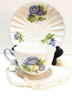 A rare Shelley tea cup and saucer in the Morning Glory pattern and Ludlow shape. Soft periwinkle morning glories circle the cup and saucer. The rims and handle are a pastel periwinkle blue. The Ludlow shape has a wide ribbed, slightly waisted cup and ribbed saucer. This set, with