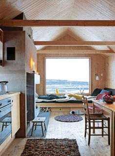 Small space, concrete fireplace, tiny kitchen, bed by the window and a little workplace - perfect tiny home.