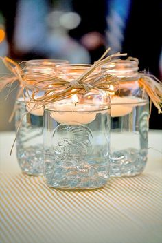 Mason jar centerpieces with floating candles. [UPDATED These DIY Mason Jar Centerpieces can also be made into favors. Use the lanterns to provide light to your wedding tables. Floating Candle Centerpieces, Rustic Wedding Centerpieces, Simple Centerpieces, Wedding Favors, Wedding Tables, Party Favors, Easy Table Decorations, Wedding Ceremony, Party Centerpieces