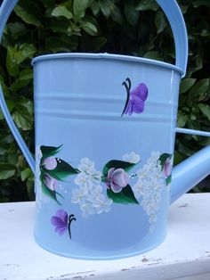 This pretty light blue enamel watering can has been hand painted with a design of pink roses, white daisies or hydrangeas, green leaves and purple butterflies along the outside of the can. A matching flower vine has also been painted on the top of the watering can. The design is