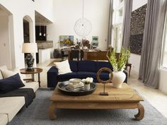 A blue-gray textured rug defines the seating area in this open concept living area. Two sofas, one in navy and one neutral, have similar contemporary lines, while the legs of the rustic coffee table add a little curve to the space.