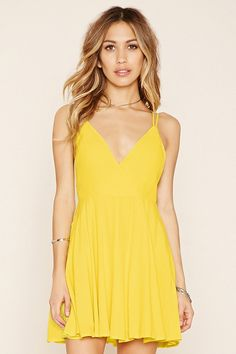 A woven mini dress with double-cami straps that crisscross in back, a V-neckline, and a concealed back zipper.