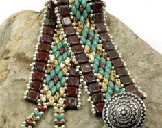 SuperDuo diamonds and Czechmate Tiles...an original design. Hand beaded in earthy tones...turquoise picasso, umber picasso, and red picasso two hole Czech pressed glass beads. These are highlighted with Miyuki duracoat galvanized muscat seed beads. These seed beads are a bright light copper color that compliment the colors of the Czech beads immensely. The clasp consists of a SuperDuo beaded loop that slides over a copper colored button with a decorative design.  When clasped the bracelet…